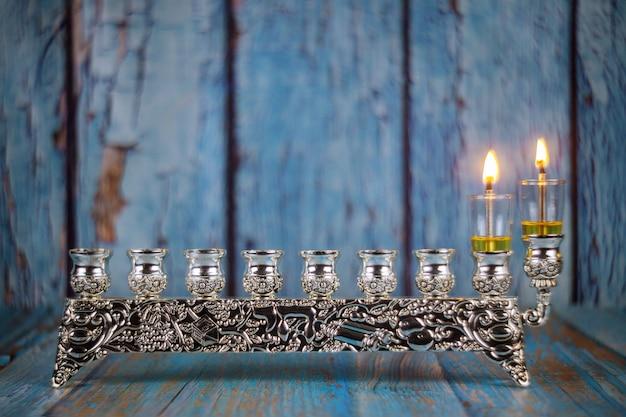 Еврейский праздник ханука с зажженной первой свечой на ханукальной меноре традиционного канделябра