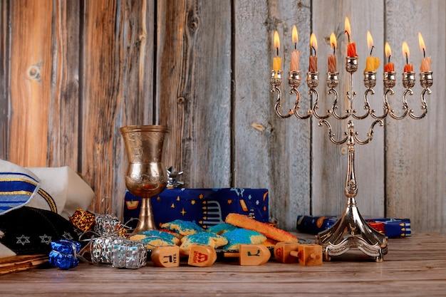ユダヤ人の祝日のハヌカ本枝の燭台の伝統的な燭台と木製のドレイドルの回転