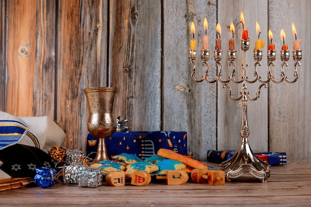 Jewish holiday hanukkah with menorah traditional candelabra and wooden dreidels spinning