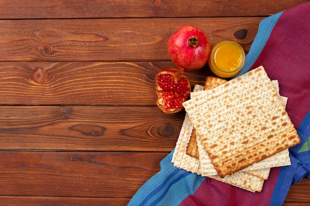 Jewish holiday passover banner design with wine, matzo on wooden table.
