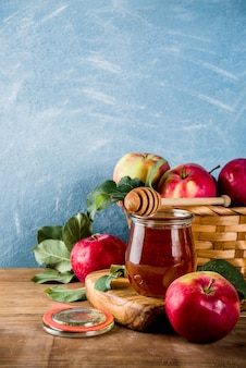 Jewish holiday rosh hashanah or apple feast day concept, with red apples, apple leaves and honey in jar