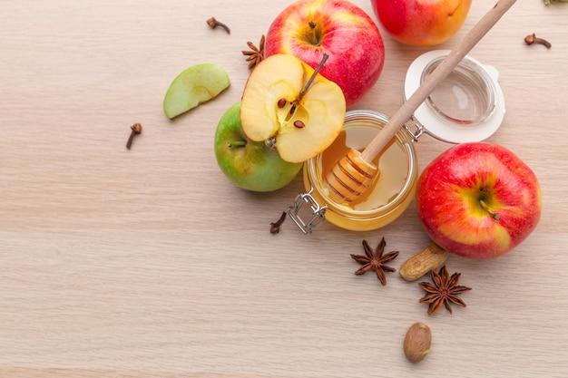 木製のテーブルに蜂蜜とリンゴとユダヤ教の祝日ロシュハシャナの背景。