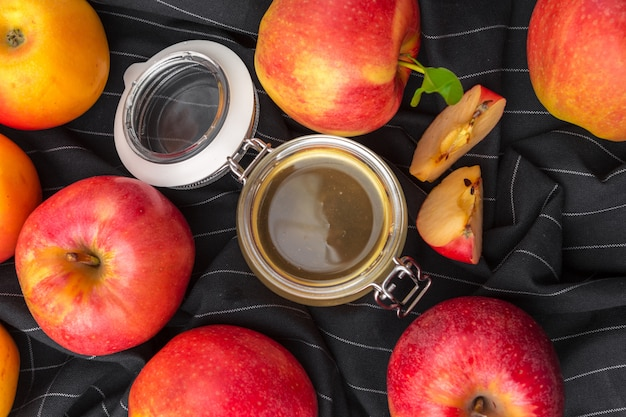 Jewish holiday rosh hashanah background with honey and apples on wooden table