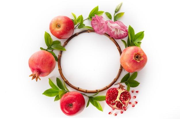 Еврейский праздник-рош ха-шана дизайн баннера с гранатами. мед и красные яблоки. вид сверху. плоская планировка