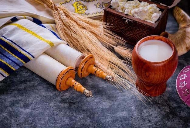 Еврейский праздник шавуот для кошерных молочных продуктов на свитке торы и таллисе