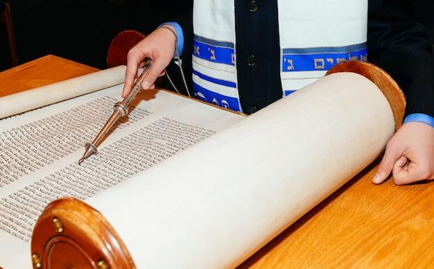 ユダヤ人の男はbar mitzvahで儀式の服torahに身を包んだ