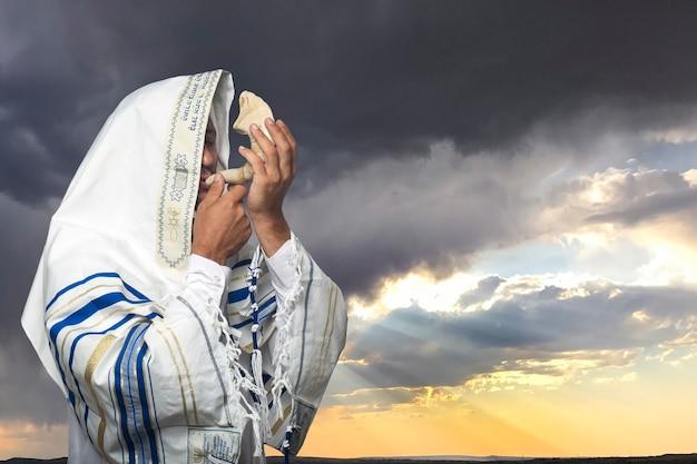 히브리어로 '바룩 아타 아도나이'라는 문구가 새겨진 기도용 목도리를 두른 유대인 남자, 로시 하샤나(설날)의 숫양 뿔인 쇼파르를 들고 극적인 일몰에 욤 키푸르를 들고 있다