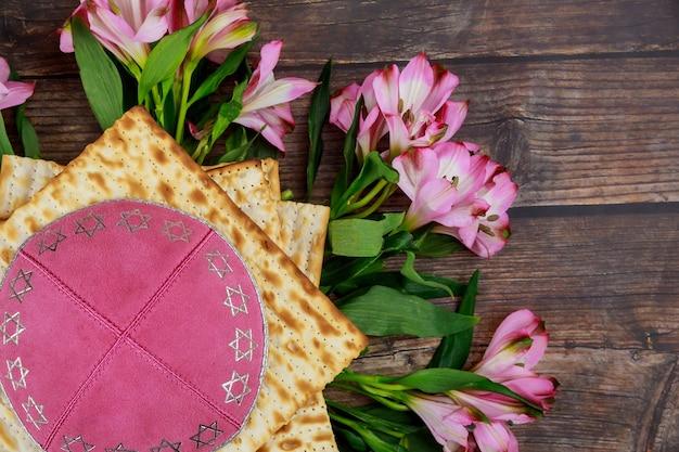 Еврейский хлеб мацы с кипой и цветами на деревянном деревенском фоне. концепция праздника пасхи.
