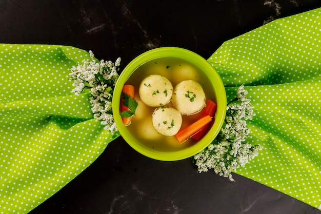 Jewish matzo ball soup with flowers for passover.