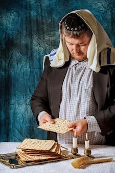 ユダヤ人の男性は、セダーを祝うマツァの種なしパンに祝福を与えています