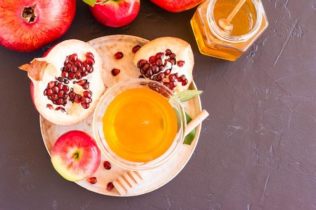 Еврейский новый год - рош ха-шана. яблоки, гранат и мед на темном фоне. традиционная еврейская еда. вид сверху, плоская планировка, место для текста.