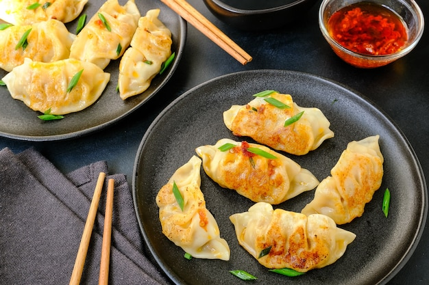 Jiaozi gyoza dumplings steamed on black plates with soy sauce and chili oil