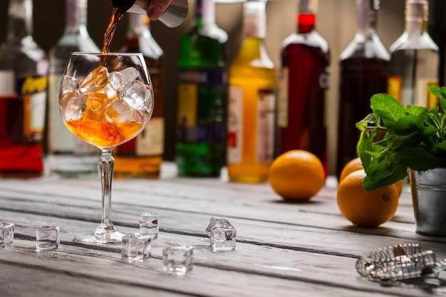 지거는 와인잔에 액체를 붓습니다. 민트와 오렌지. 클럽에서 음료를 준비 중입니다. 고품질의 수입 럼.