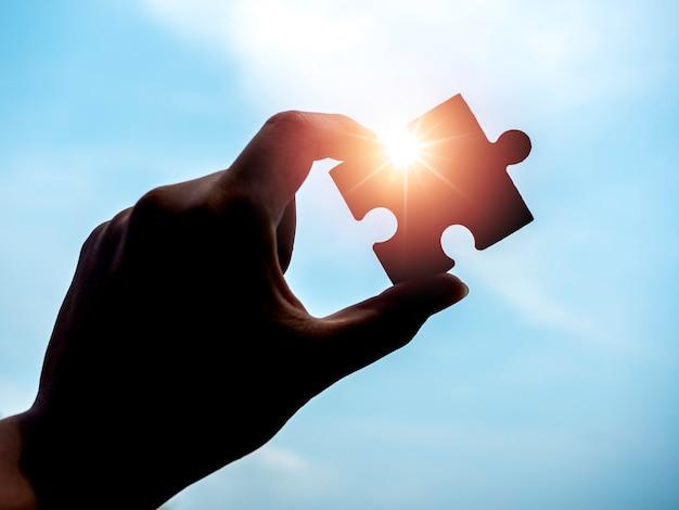青い空を背景にジグソー パズル、シルエット。太陽光と太陽光線でパズルのピースを持つビジネスマンの手。ビジネス ソリューション、成功、パートナーシップ、戦略のコンセプト。