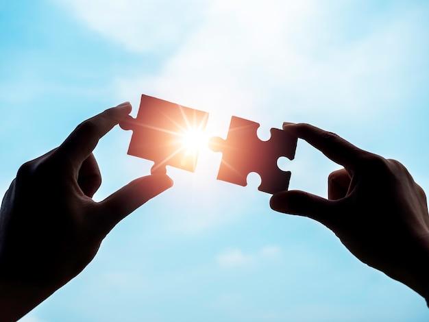 青い空を背景にジグソー パズル、シルエット。 2 つのパズルのピースを太陽光と太陽光線でつなぐビジネスマンの 2 つの手。ビジネス ソリューション、成功、パートナーシップ、戦略のコンセプト。