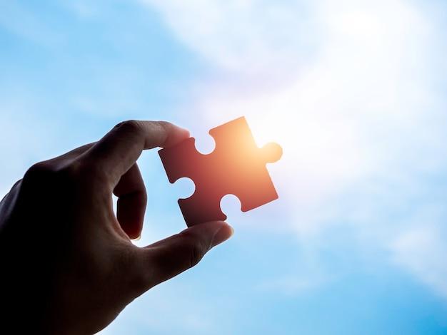 青い空を背景にジグソー パズル、コピー スペース、シルエット。太陽の光でパズルのピースを持つビジネスマンの手。ビジネス ソリューション、成功、パートナーシップ、戦略のコンセプト。