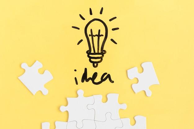 직소 퍼즐 및 노란색 배경에 아이디어 단어로 전구