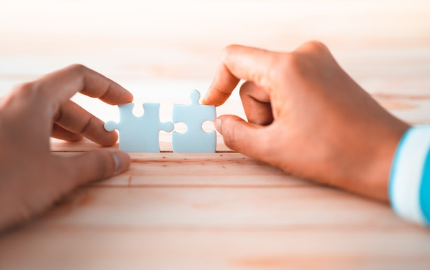 Jigsaw puzzle connecting by two hands, solution to success concept