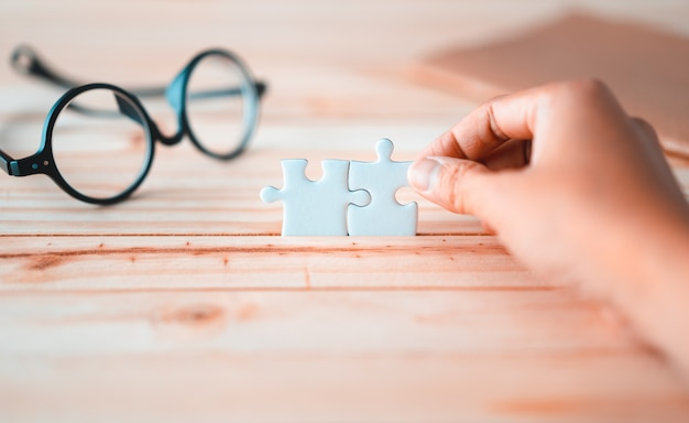 Jigsaw puzzle holding by hand on wooden table with blurred glasses and brown notebook