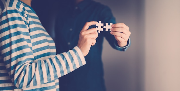 Jigsaw puzzle holding by two people hands