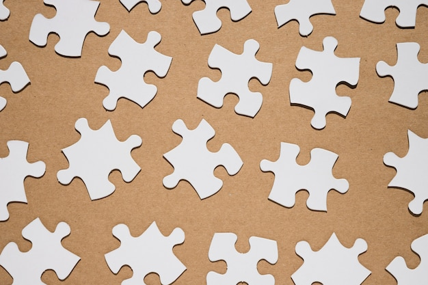 Jigsaw puzzle pieces on brown paper textured backdrop