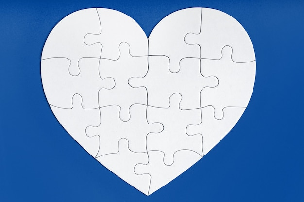 Jigsaw puzzle pieces in form of heart on blue