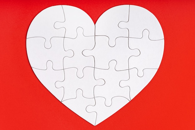 Jigsaw puzzle pieces in form of heart on red space.