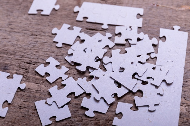 Jigsaw puzzle pieces lying on old wooden rustic boards. conceptual of innovation, solution finding and integration.