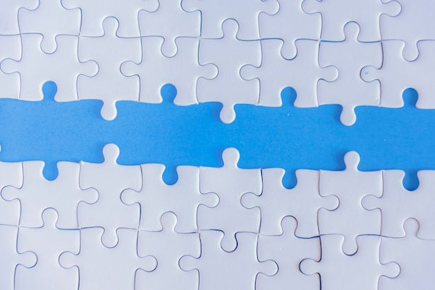 Jigsaw puzzle white on blue background.