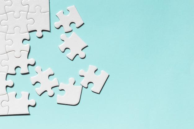 파란색 배경에서 직소 퍼즐 흰색 조각