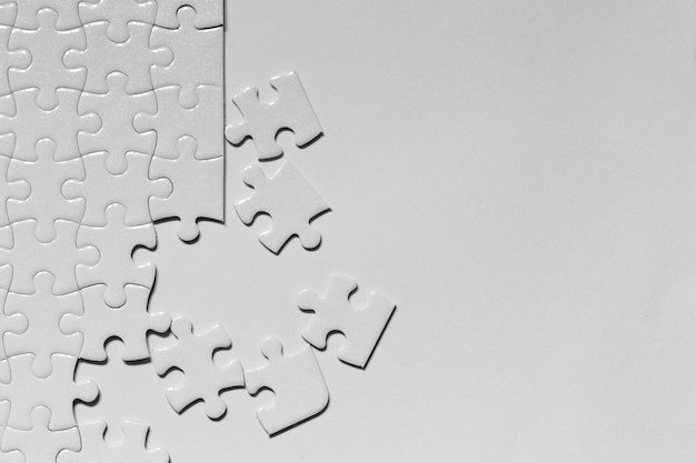 Jigsaw puzzle white piece on white backdrop
