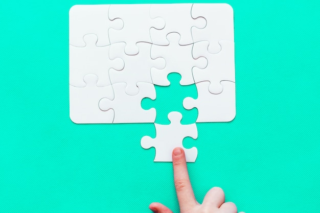 Jigsaw puzzle with missing piece on mint background people hand