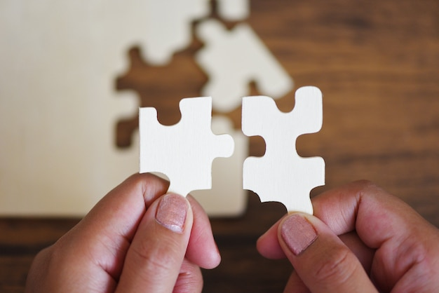 Jigsaw puzzle with woman hand connecting jigsaw piece