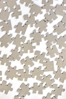 Jigsaw puzzles background. close up variety of grey puzzle pieces over white background.