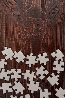 직소 퍼즐 부품 및 복사 공간. 나무 배경 및 텍스트 공간에 빈 골 판지 퍼즐.