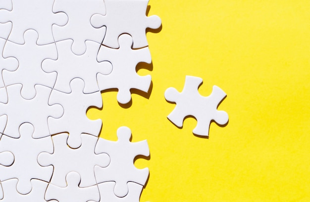 Jigsaw puzzles pieces on illuminating yellow background