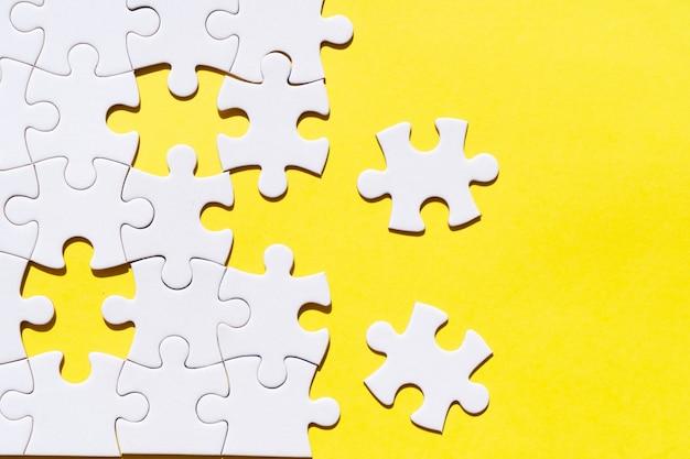 ジグソーパズルは、黄色の背景を照らす上で未分類のピースをパズルします