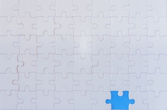 Jigsaw with one piece missing revealing Blue background