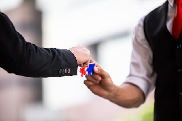 Руки деловых людей держать документ головоломки вместе, сбор бизнес-команды jigsaw