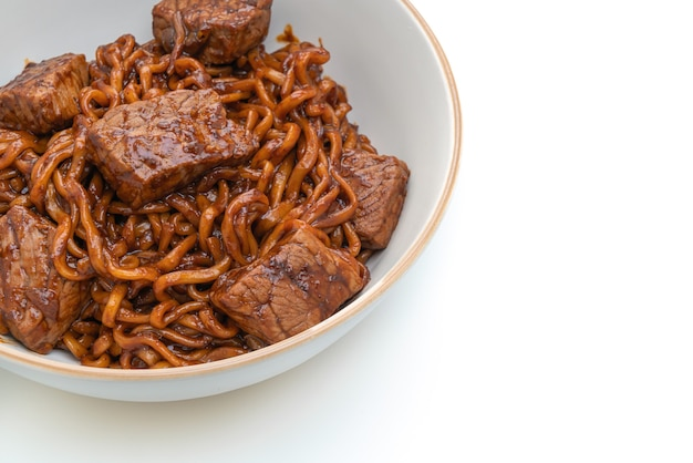Jjapaguri or chapaguri, korean black beans spicy noodles with beef isolated on white surface