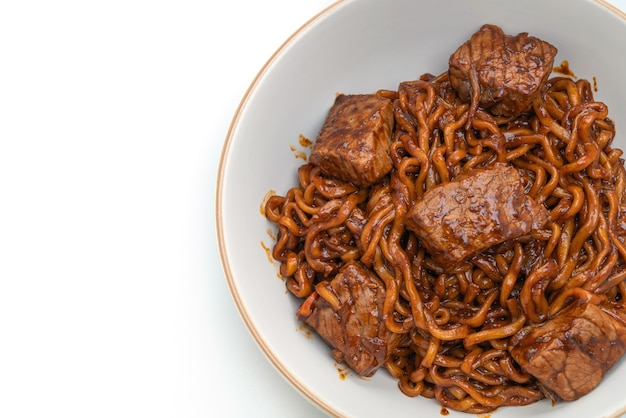 Jjapaguri or chapaguri, korean black beans spicy noodles with beef isolated