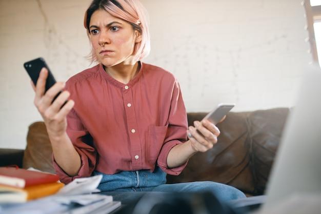 Профессиональное выгорание. разозленная переутомленная бизнесвумен в повседневной одежде пытается справиться с внештатной работой из-за социального дистанцирования, держит в руках два звонящих телефона, увлеченная множеством задач