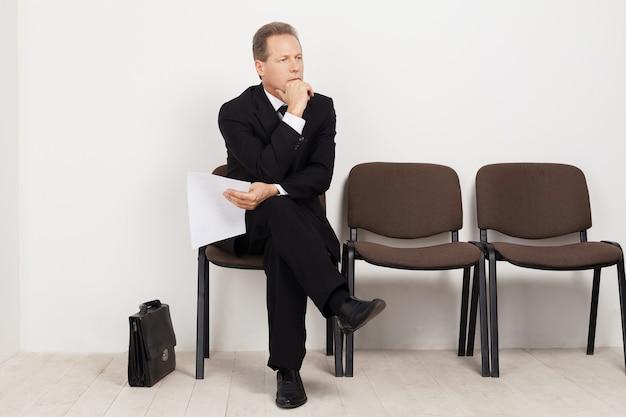 Кандидат на работу. скучающий зрелый мужчина в строгой одежде держит бумагу и скрещивает ноги в коленях, сидя на стуле в зале ожидания