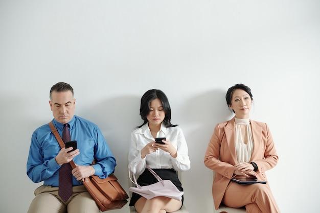 사무실 복도의 의자에 앉아 인사 관리자와의 인터뷰를 기다리는 구직자