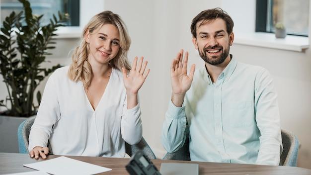 手を振って机に座っている仕事仲間
