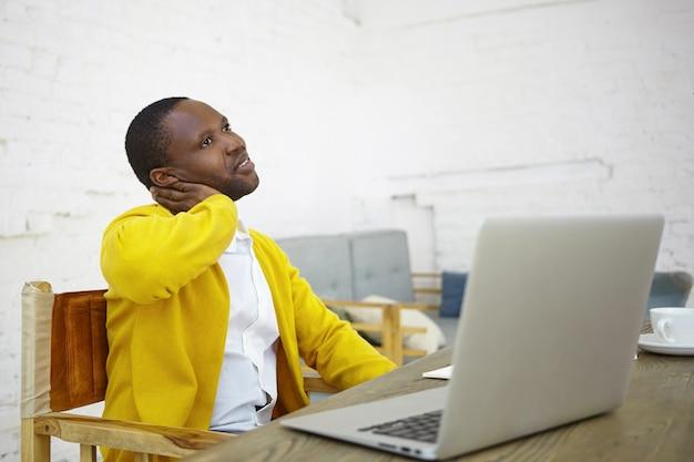 仕事、創造性、職業、フリーランスのコンセプト。物思いにふける外観を持つスタートアッププロジェクトに取り組んでいる机の開いたラップトップの前に座っているスタイリッシュな繁栄の暗い肌の男性起業家の肖像画