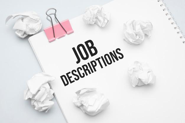 Описание вакансии. чистый лист бумаги, красная канцелярская скрепка, словесные идеи и скомканные бумажные комочки