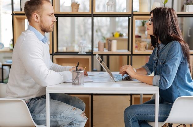 Собеседование. уверенная в себе умная привлекательная бизнес-леди смотрит на соискателя и работает за ноутбуком во время собеседования с ним