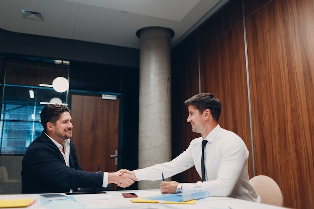 Собеседование при приеме на работу с деловыми людьми, которые разговаривают о встрече в офисе и обмениваются рукопожатием с человеческими ресурсами ...