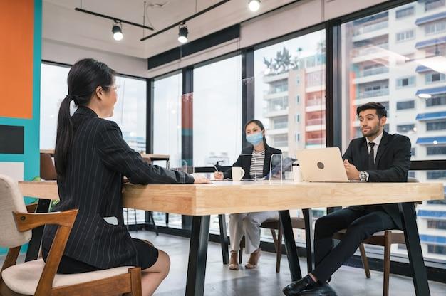 Собеседование кавказского кадрового работодателя с секретарем и молодой азиатской женщиной-кандидатом в современном офисе